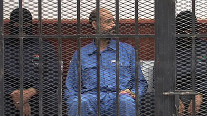 Seif al-Islam, son of Libya's late dictator Muammar Gaddafi, looks on in the accused cell as he stands trial for illegally trying to communicate with the outside world in June last year, on May 2, 2013 in Libya's northwestern town of Zintan. (AFP Photo)