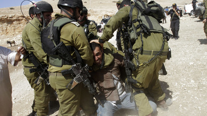 Israeli soldiers detain a Palestinian during scuffles following an attempt by European diplomats to deliver goods to locals in the West Bank herding community of Khirbet al-Makhul, in the Jordan Valley September 20, 2013. (Reuters/Abed Omar Qusini)