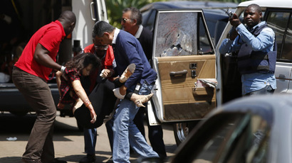 Emergency services carry a woman to an ambulance in the car park as police search through the Westgate shopping centre for gunmen in Nairobi, September 21, 2013. (Reuters/Goran Tomasevic)