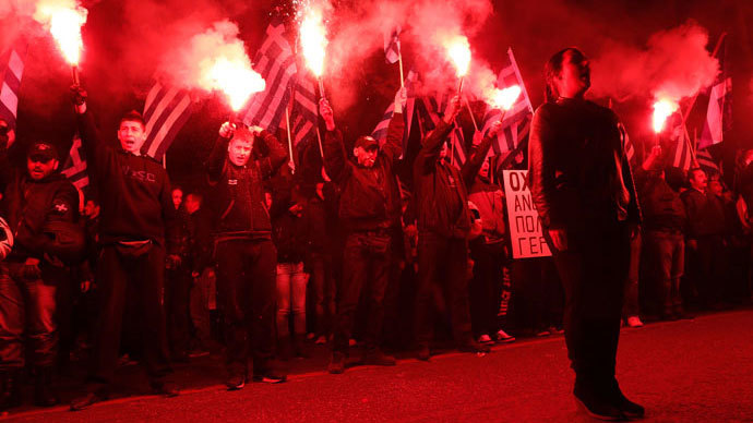 Supporters of the extreme-right Golden Dawn party hold flares as they chant the national anthem, during a rally over the crisis in Cyprus, outside the German embassy in Athens March 22, 2013. (Reuters / John Kolesidis)