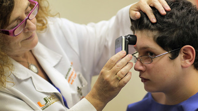 Doctor Antonella Tosti, Dermatologist University of Miami School of Medicine, uses an iphone as a dermatoscope as she examines Michael Casa Nova,12, for symptoms of skin cancer due to sun exposure (Joe Raedle/Getty Images/AFP)