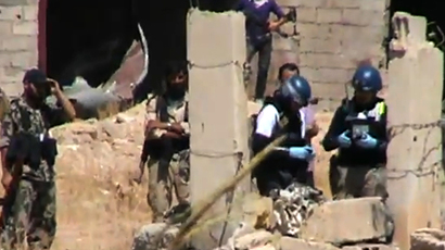 An image grab taken from a video uploaded on YouTube by Harasta Media Centre on August 28, 2013 allegedly shows opposition fighters standing next to a United Nations (UN) arms expert as they collect information during an investigation into a suspected chemical weapons attack in Damascus' eastern Ghouta suburb. (AFP Photo)