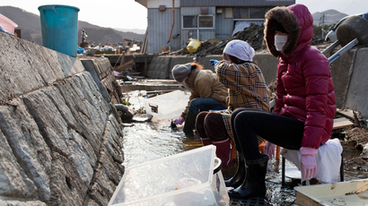 Japanese women wash their salvaged belongings in a stream due to lack of water in the tsunami-devastated town of Rikuzentakata, Iwate prefecture, on April 2, 2011 (AFP Photo / Yasuyoshi Chiba)
