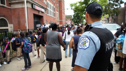 Chicago Probationary Police officer Juan Soto watches as students leave Laura Ward Elementary school on the Westside on August 28, 2013 in Chicago.(AFP Photo /  Scott Olson)