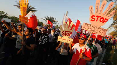 "Anti-government protesters holding banners saying ""Stop Dictatorship In Bahrain"" as they participate in a rally called by Bahrain's main opposition Al Wefaq in Budaiya, west of Manama, September 27, 2013 (Reuters / Hamad I Mohammed)"