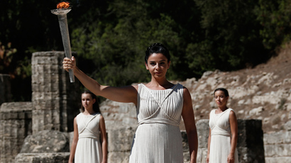 Greek actress Ino Menegaki (front), playing the role of High Priestess, raises a torch with the Olympic flame during a lighting ceremony of the Sochi 2014 Winter Olympic Games at the site of ancient Olympia in Greece September 29, 2013 (Reuters / Yorgos Karahalis)