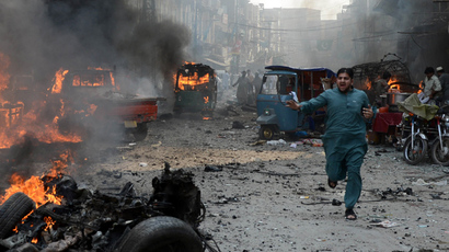 A Pakistani man runs past burning vehicles at the site of a bomb explosion in the busy Kissa Khwani market in Peshawar on September 29, 2013 (AFP Photo / Hasham Ahmed)