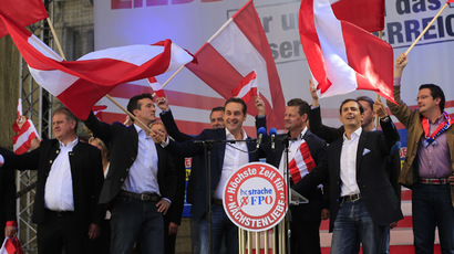 Heinz-Christian Strache (C) candidate of the Freiheitliche Partei Oesterreichs FPO Party (Freedom Party of Austria) waves flags during a meeting of the FPO political party in Klagenfurt on September 14, 2013 ahead of the Austrian legislative elections taking place on September 29, 2013. (AFP Photo/Alexander Klein)
