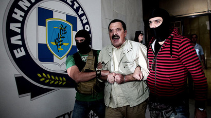 Christos Pappas (C), lawmaker of the extreme far-right Golden Dawn party, is escorted by masked police officers to the prosecutor's office from the police headquarters in Athens on September 29, 2013 (AFP Photo / Angelos Tzortzinis)