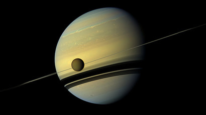 A giant of a moon appears before a giant of a planet undergoing seasonal changes in this natural color view of Titan and Saturn from NASA's Cassini spacecraft (AFP Photo / NASA / JPL)