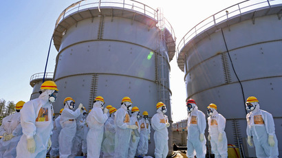 Japanese Prime Minister Shinzo Abe (3rd R) is briefed about tanks containing radioactive water by Fukushima Dai-ichi nuclear power plant chief Akira Ono (4th L) in front of two tanks (back) which are being dismantled after leaking contaminated water, during his tour to the tsunami-crippled plant in Okuma, Fukushima Prefecture, northeastern Japan on September 19, 2013. (AFP Photo/Japan Pool)