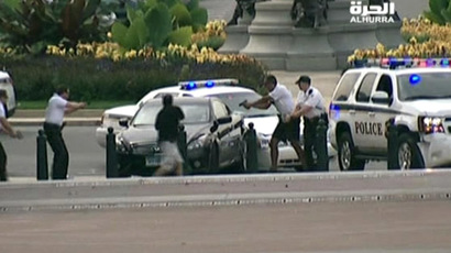 U.S.Capitol Police surround a car with their guns drawn at the corner of Pennsylvania Avenue and 1st Street, northwest in this framegrab from Alhurra TV video taken just before a shooting in Washington, October 3, 2013. (Reuters/Alhurra)