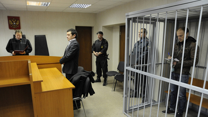 The photographer Denis Sinyakov (R) charged wirh an illegal attempt at penetrating the Prirazlomnaya oil platform, attending hearings on his pre-trail detention measure at the Leninsky Court, Murmansk (RIA Novosti / Sergey Eshenko)