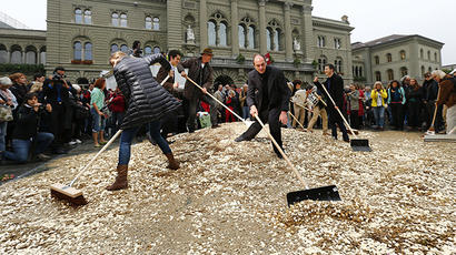 "Committee members use brooms and shovels to spread out five cent coins over the Federal Square during an event organised by the Committee for the initiative ""CHF 2,500 monthly for everyone"" (Grundeinkommen) in Bern October 4, 2013. (Reuters / Denis Balibouse)"