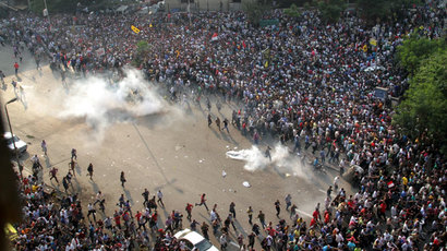 Egyptian Muslim brotherhood and supporters of ousted president Mohamed Morsi run for cover from tear gas during clashes with riot police along Ramsis street in downtown Cairo, on October 6, 2013. ( AFP Photo / Ahmed Gamel)