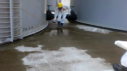 This handout picture taken by Tokyo Electric Power Co (TEPCO) on August 22, 2013 shows a TEPCO worker checking radiation levelS around a contaminated water tank at TEPCO's Fukushima Dai-ichi nuclear power plant at Okuma town in Fukushima prefecture. (AFP/TEPCO)