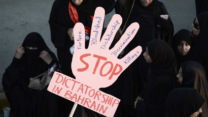 Bahraini women hold a placard reading 'Stop dictatorship in Bahrain' as they take part in an anti-government protest in the village of Jannusan, west of the capital Manama, on September 27, 2013. (AFP Photo)
