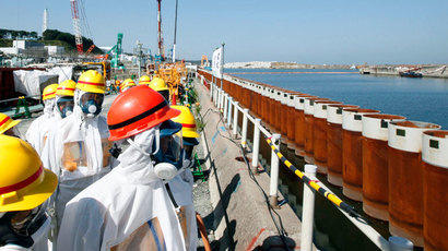 Japan's Prime Minister Shinzo Abe (red helmet), wearing protective suit and mask, looks at an impervious wall made of steel pipe sheet pile installed along the coast during his inspection tour to the Tokyo Electric Power Co. (TEPCO)'s tsunami-crippled Fukushima Daiichi nuclear power plant in Okuma, Fukushima Prefecture, September 19, 2013.(Reuters / Pool)