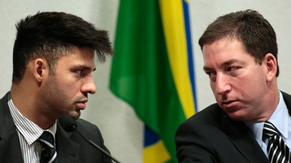 Glenn Greenwald (R), American journalist who first published the documents leaked by former NSA contractor Edward Snowden, speaks with partner David Miranda as Greenwald testifies in front of the Brazilian Federal Senate's Parliamentary Inquiry Committee, established to investigate allegations of spying by United States on Brazil, in Brasilia October 9, 2013 (Reuters / Ueslei Marcelino)