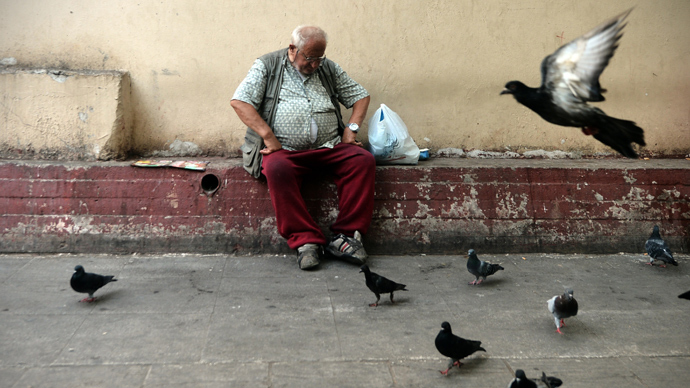 A man sits next to pigeons after he received food donated by the Greek church in central Athens (AFP Photo / Aris Messinis)