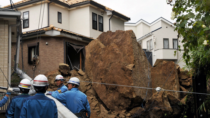 A house and an electric pole smashed by large rocks from a collapsed slope caused by heavy rain in Kamakura, suburban Tokyo on October 16, 2013 (AFP Photo / Jiji Press)