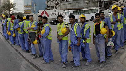 Foreign workers wait for their bus at a construction site in front World Trade centre tower in Doha (Reuters /  Fadi Al-Assaad)