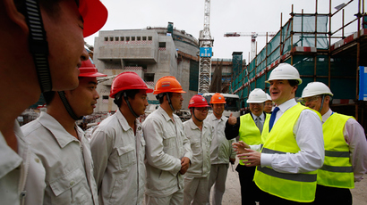 British Chancellor of the Exchequer George Osborne (2-R) chats with workers beside Taishan Nuclear Power Joint Venture Co Ltd General Manager Guo Liming (3-R) and EDF Energy CEO Vincent de Rivaz (R), in front of a nuclear reactor under construction at a nuclear power plant in Taishan, Guangdong province, October 17, 2013 (Reuters / Bobby Yip)