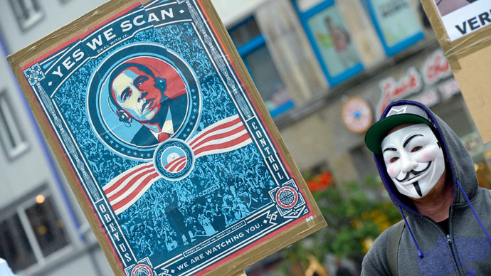 "protestor wearing a Guy-Fawkes-mask holds a banner with a picture of US President Barack Obama to protest against the NSA internet surveillance programme ""PRISM"" on June 29, 2013 in Hannover, central Germany. (AFP/DPA)"