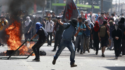 Student protesters clash with riot policemen during a demonstration against the government to demand changes in the public state education system in Santiago, October 17, 2013.  (Reuters//Ivan Alvarado)
