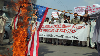 Pakistani protesters belonging to United Citizen Action march behind a burning US flag during a protest in Multan on September 30, 2013, against the US drone attacks in Pakistani tribal areas (AFP Photo / S.S Mirza)