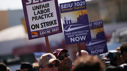 Demonstrators hold signs in support of striking Bay Area Rapid Transit (BART) workers outside Lake Merritt Station in Oakland, California October 18, 2013 (Reuters / Stephen Lam)