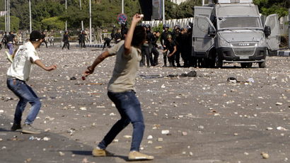 Protesters throw stones during clashes with riot police in front of the main offices of Al-Azhar University in Cairo October 20, 2013 (Reuters / Mohamed Abd El Ghany)