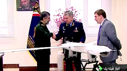 "The head of the aerospace forces of Iran's Revolutionary Guards, General Amir Ali Hajizadeh (L) handing a copy of the Iranian drone ""Yassir"" ScanEagle to the head of the Russian Air Force, General Viktor Bondarev (C) in Tehran on October 21, 2013. (Iranian State TV video still)"