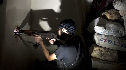 Opposition fighter Abu Yassin, 21, takes position inside a building in Salaheddin square, in Syria's northern city of Aleppo (AFP Photo / Jm Lopez)