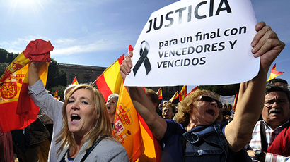 "People brandish Spanish flags and a poster reading ""Justice, for a end with winners and losers"" as they gather with thousands of Spaniards at Plaza de Colon on October 27, 2013. (AFP Photo / Gerard Julien)"