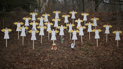 Twenty-seven wooden angel figures are seen placed in a wooded area beside a road near the Sandy Hook Elementary School for the victims of a school shooting in Newtown, Connecticut December 16, 2012. (Reuters/Mike Segar)