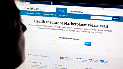"A woman looks at the HealthCare.gov insurance exchange internet site showing a ""Please wait"" page, in this October 1, 2013 file photo in Washington, DC. (AFP Photo / Karen Bleier)"