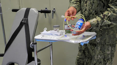 A US naval medic holds liquid food supplement force fed to hunger strikers at the US Naval Base in Guantanamo Bay, Cuba on August 7, 2013. (AFP Photo)