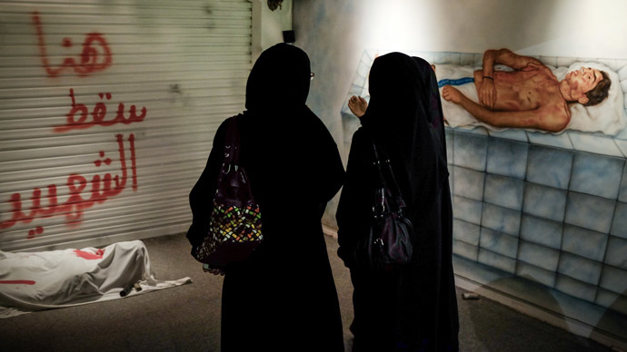 "Bahraini women stand in front of an art installation at the ""revolution museum"" on October 28, 2013 in Manama. (AFP Photo)"