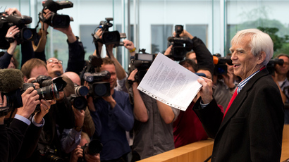 German Green party parliamentarian Hans-Christian Stroebele holds up a letter as he arrives to address a press conference in Berlin on November 1, 2013 (AFP Photo / John Macdougall)