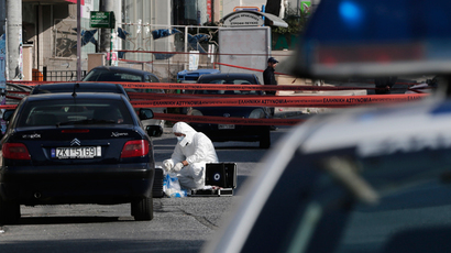 A police forensic expert searches for evidence outside the local offices of far-right Golden Dawn party, following last night's shooting, in a northern suburb of Athens November 2, 2013 (Reuters / John Kolesidis)