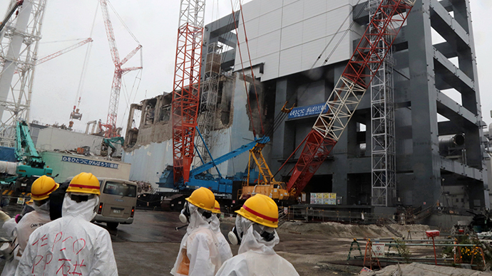 (FILE) Tokyo Electric Power Co workers look up the unit 4 reactor building during a media tour at TEPCO's Fukushima Dai-ichi nuclear plant in the town of Okuma, Fukushima prefecture in Japan (AFP Photo / Noboru Hashimoto)