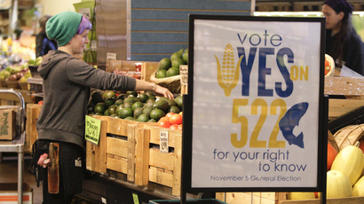An employee stocks produce near a sign supporting a ballot initiative in Washington state that would require labeling of foods containing genetically modified crops at the Central Co-op in Seattle, Washington October 29, 2013.  (Reuters/Jason Redmond)