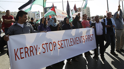 Palestinian protesters hold flags and a banner during a demonstration against U.S. Secretary of State John Kerry's visit, in the West Bank town of Bethlehem November 6, 2013. (Reuters / Mohamad Torokman)