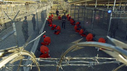 Detainees in orange jumpsuits sit in a holding area under the watchful eyes of military police during in-processing to the temporary detention facility at Camp X-Ray of Naval Base Guantanamo Bay in this January 11, 2002 file photograph. (Reuters)