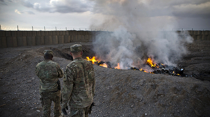 U.S. Army soldiers watch garbage burn in a burn-pit at Forward Operating Base Azzizulah in Maiwand District, Kandahar Province (Reuters / Andrew Burton)