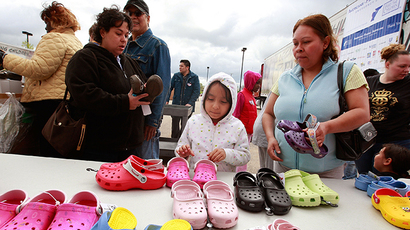 Families search through shoes donated by Crocs at a distribution site for Feed The Children (AFP Photo / Scott Olson)