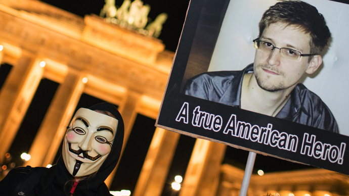"A supporter of the Anonymous group wearing a Guy Fawkes mask holds up a placard featuring a photo of US intelligence leaker Edward Snowden and reads ""A true American Hero!"" during a rally in front of Berlin's landmark Brandenburg Gate on November 5, 2013. (AFP Photo / DPA / Florian Schun / Germany out)"