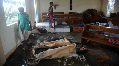 Relatives of the flood victims look at the dead bodies inside a chapel near the Tacloban Airport, eastern island of Leyte on November 9, 2013. (AFP Photo / Noel Celis)
