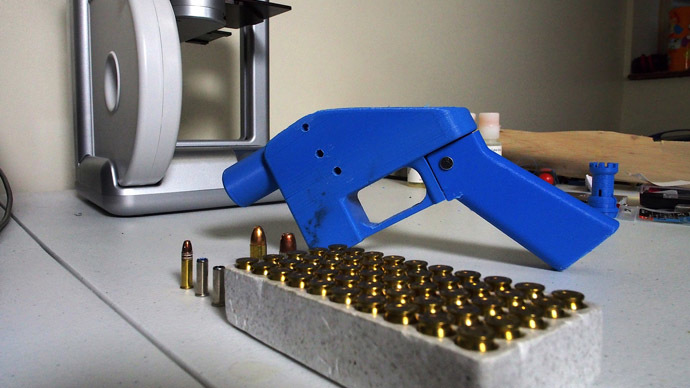 A Liberator pistol appears on July 11, 2013 next to the 3D printer on which its components were made. (AFP Photo/Robert MacPherson)